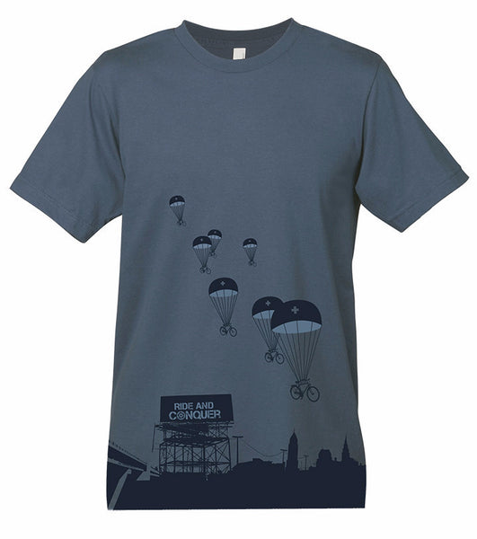 "A blue gray t-shirt with a graphic of parachutes and bicycles. At the bottom of the t-shirt is a cityscape with a billboard that says ""Ride and Conquer"""