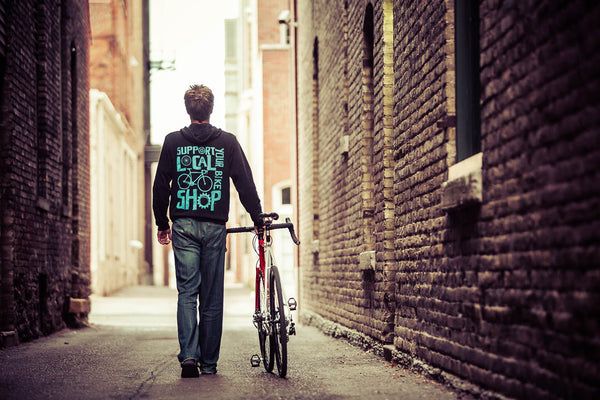 Lifestyle image of a man and his bike wearing the black shop local hoodie.