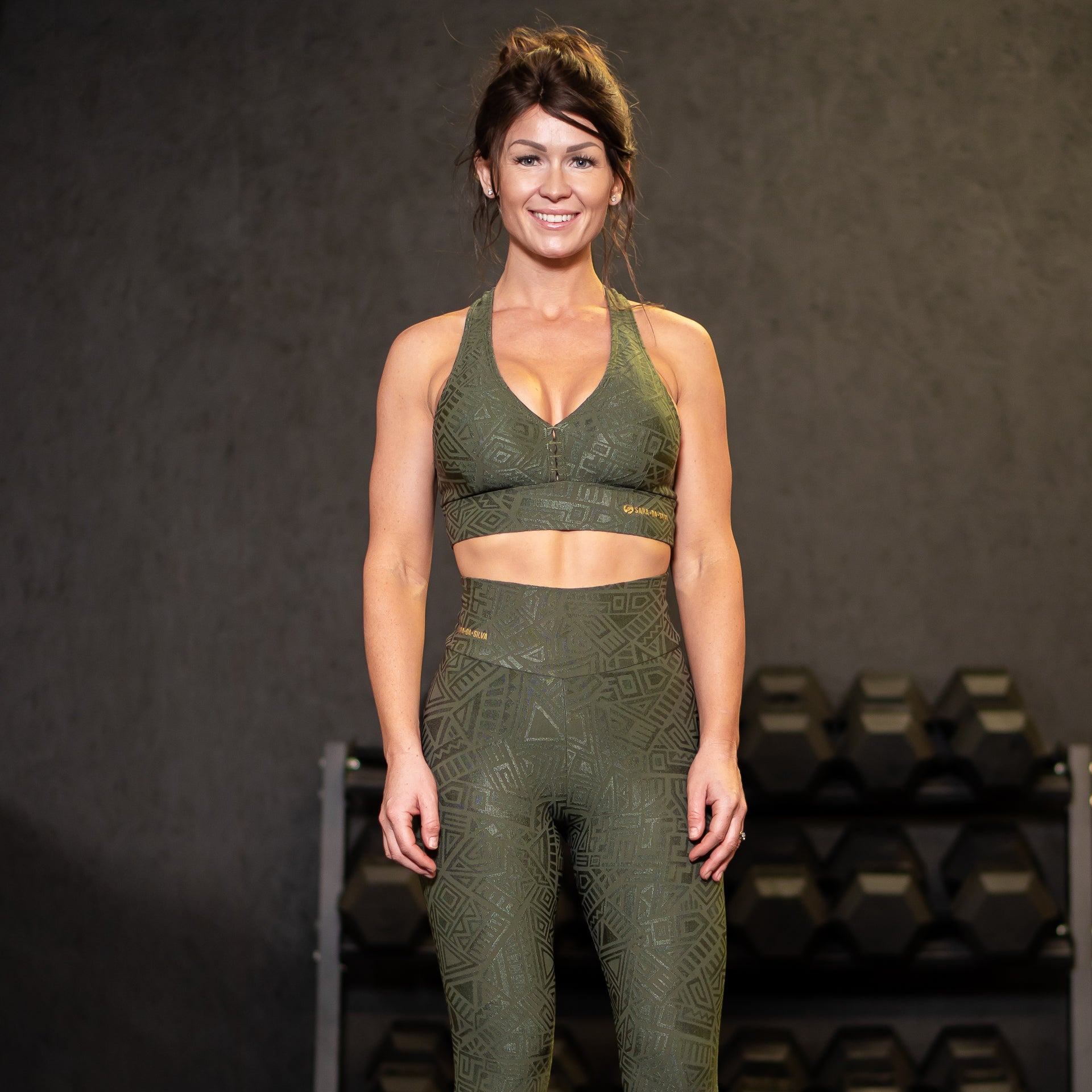 A fit lady with brown hair in a gym wearing khaki green leggings and a sports bra from the Sara Da Silva tribe collection.