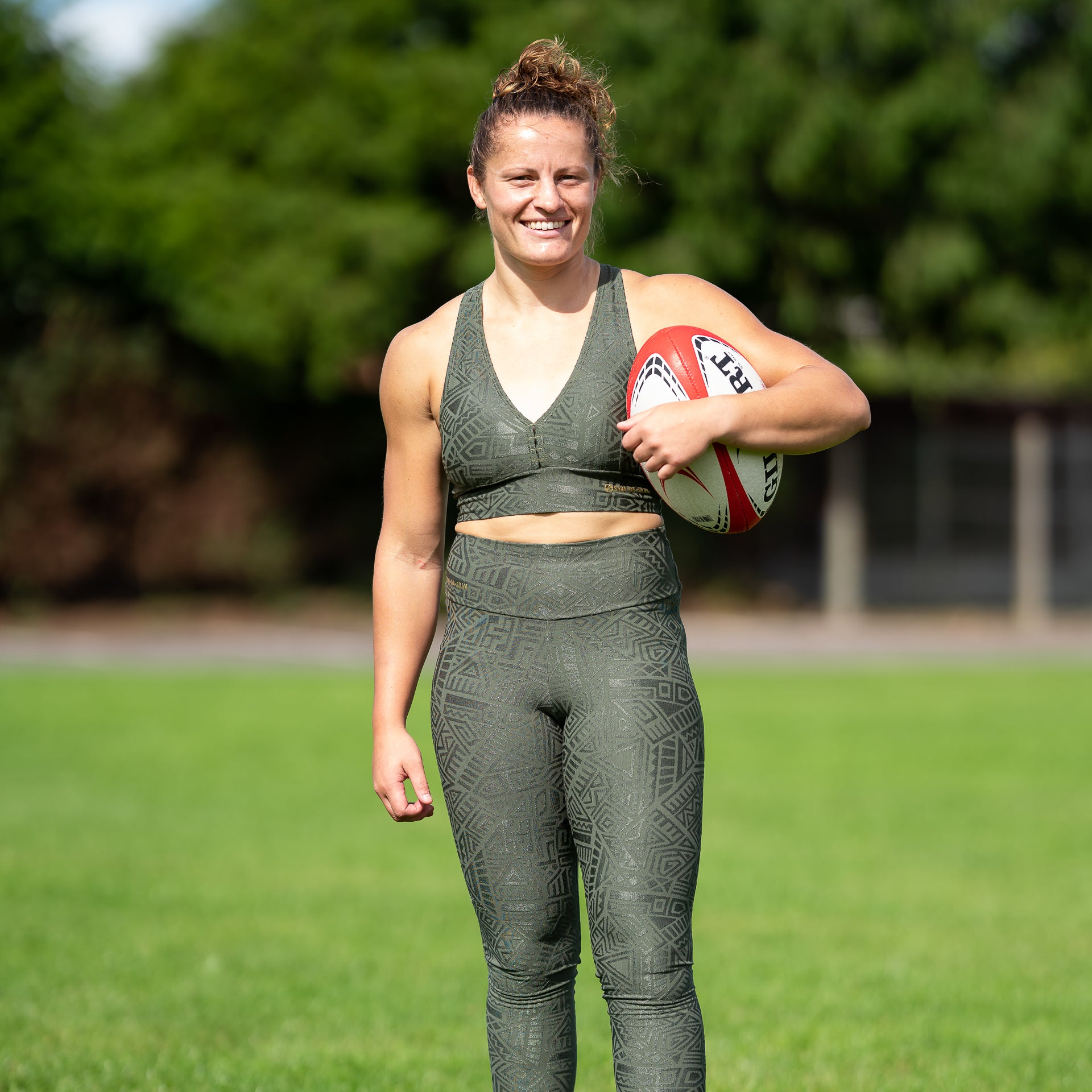 A fit lady with brown curly hair standing on a rugby pitch wearing khaki green leggings and a sports bra from the Sara Da Silva tribe collection.