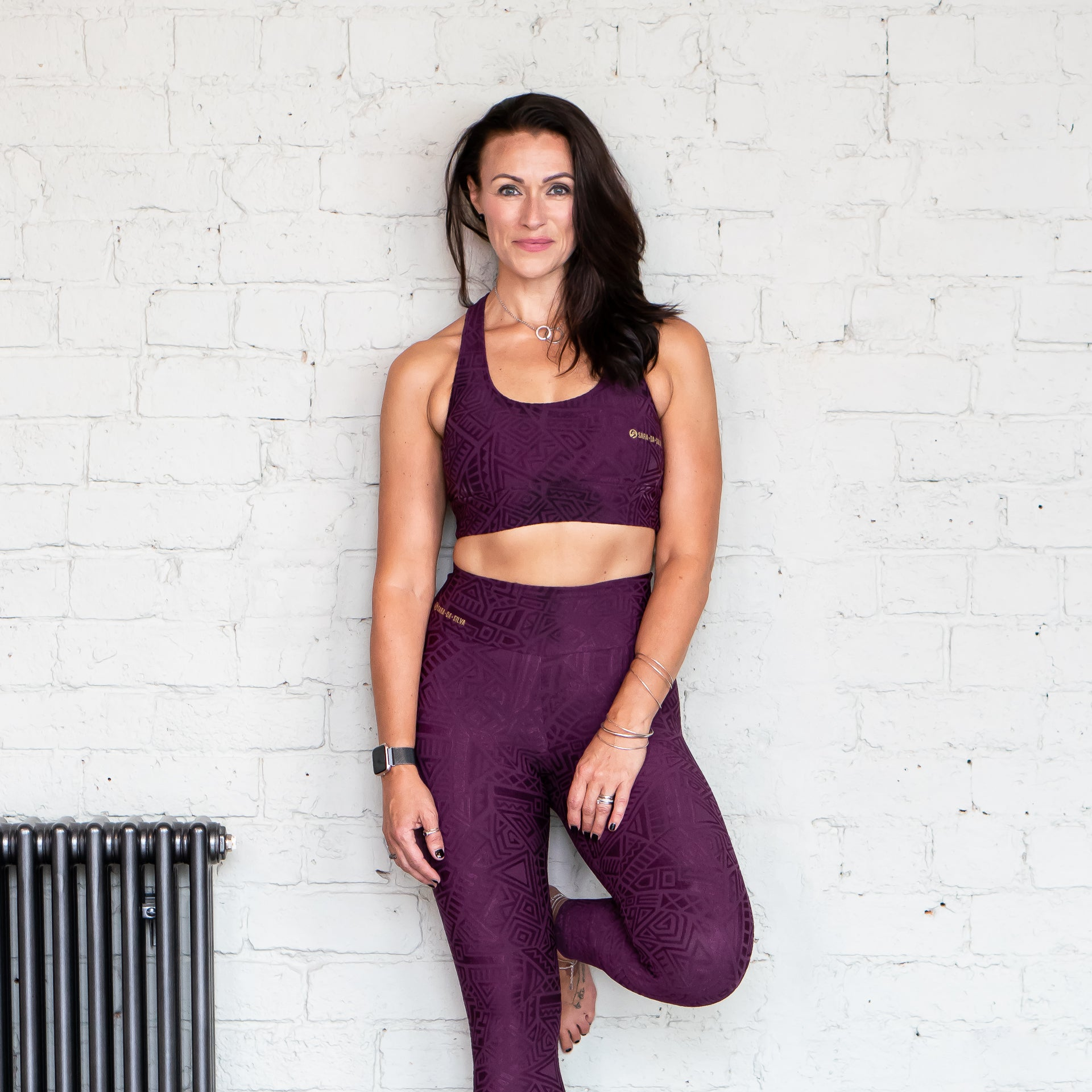 A fit lady with brown hair leaning against a brick wall wearing purple leggings and a sports bra from the Sara Da Silva tribe collection.