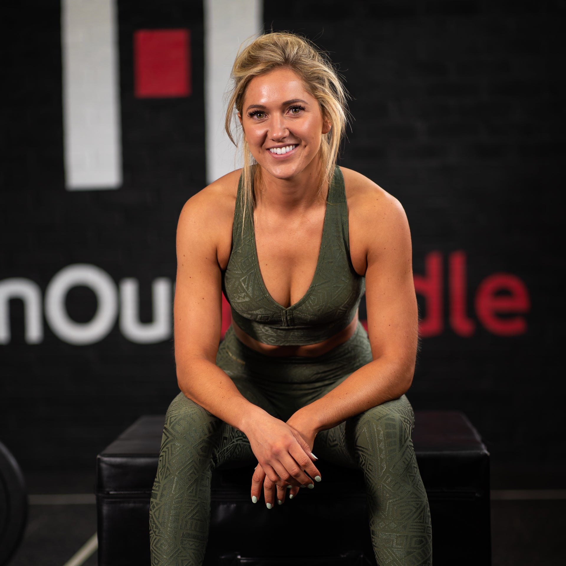 A fit lady with blonde hair in a gym wearing khaki green leggings and a sports bra from the Sara Da Silva tribe collection.