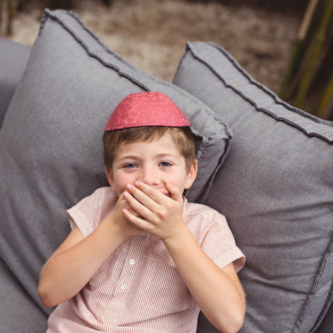 A boy laughing while sitting on a grey couch wearing a red iKIPPAH.