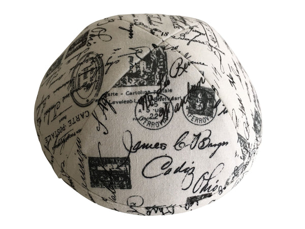 A black & white iKIPPAH brand yarmulke that has postmarks and stamps.