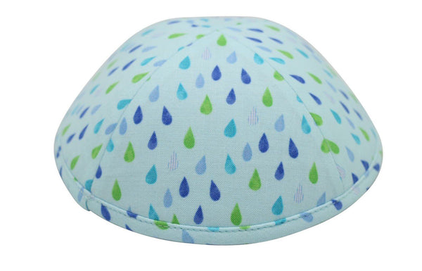 An iKIPPAH brand yarmulke in light blue with a variety of blue & green small rain drops on the fabric.