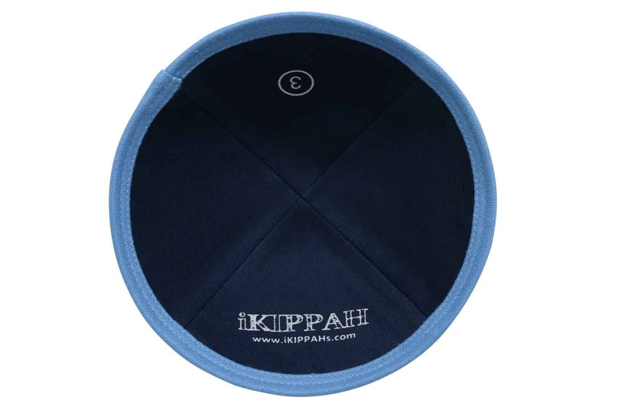 A navy blue iKIPPAH brand yarmulke with a light blue bottom trim rim.