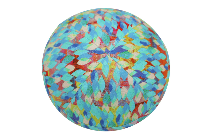 A beautiful light blue iKIPPAH brand yarmulke with red & yellow accents all in the style of abstract kites.