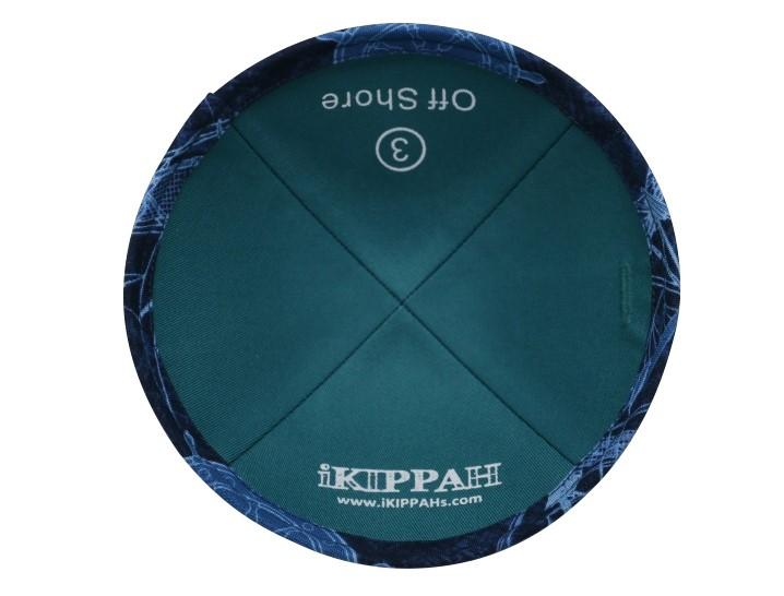 A dark blue iKIPPAH brand yarmulke with light blue nautical images on it.