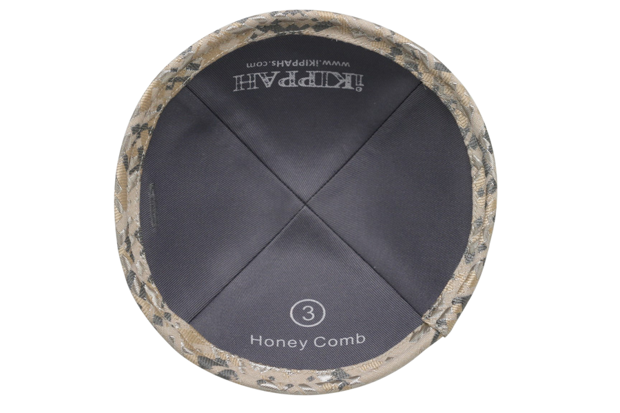 A light gold & grey patterned iKIPPAH brand yarmulke that looks like a bee honey comb.