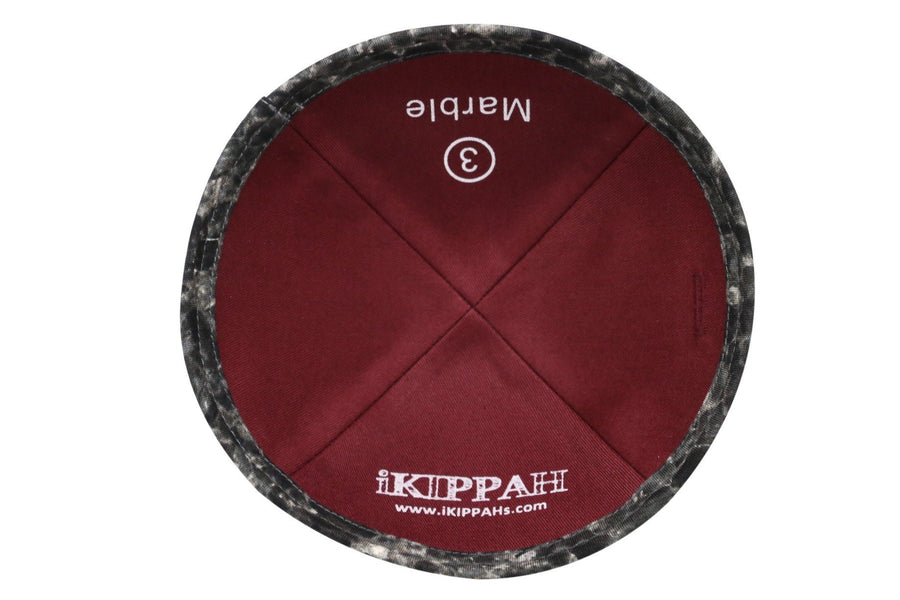A black iKIPPAH brand yarmulke that has a pattern resembling marble stone.