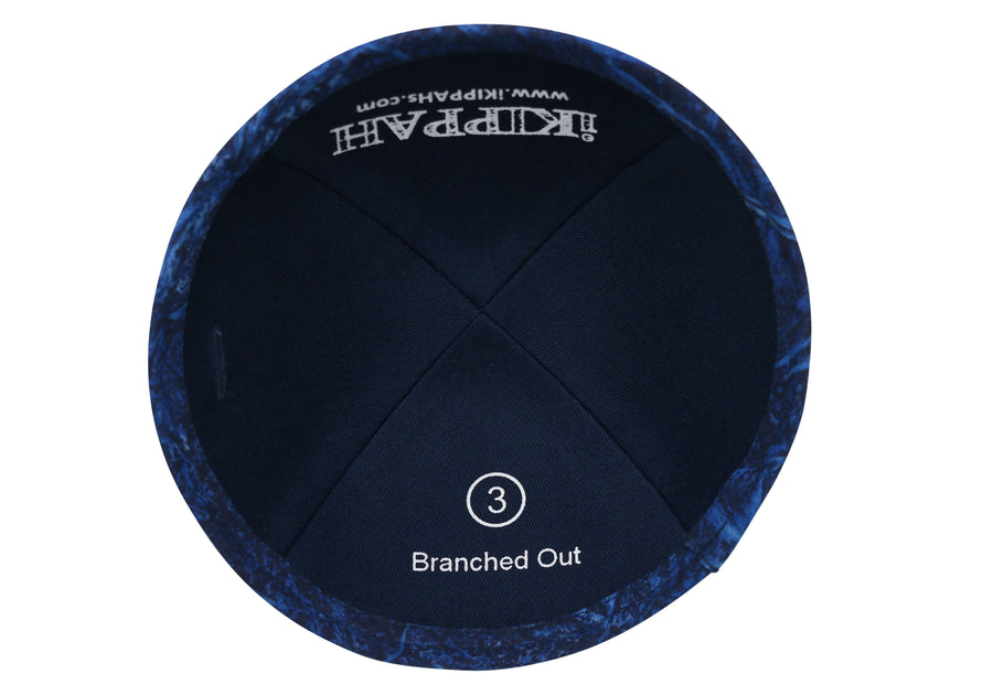 A blue iKIPPAH brand yarmulke that contains an artist's rendition of light colored branches intermingling.