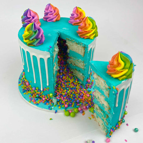 Piñata Cake one slice cut out with candy pouring out
