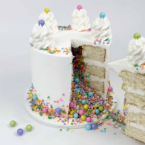 Piñata Sprinkle Cake, a slice cut out with candy pouring out