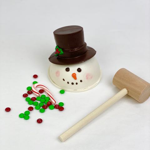 Snowman Chocolate Pinata, red and green M&Ms, candy cane and a mallet