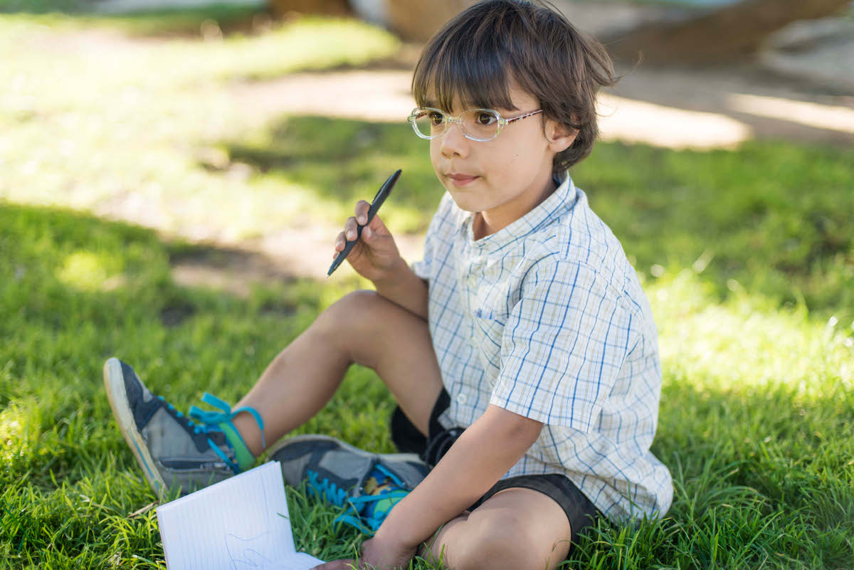 Boy wearing glasses and holding a notepad