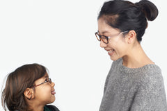 Woman and a young child wearing glasses looking at each other