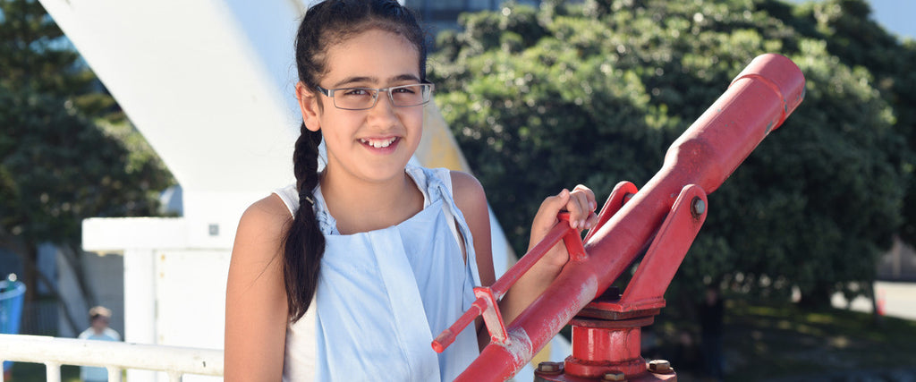 Child wearing metal glasses frames standing by a red telescope