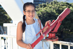 Girl wearing glasses standing by a telescope