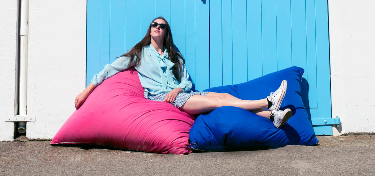 Woman lying back on bean bags against Wellington boat sheds wearing Mr Foureyes sunglasses