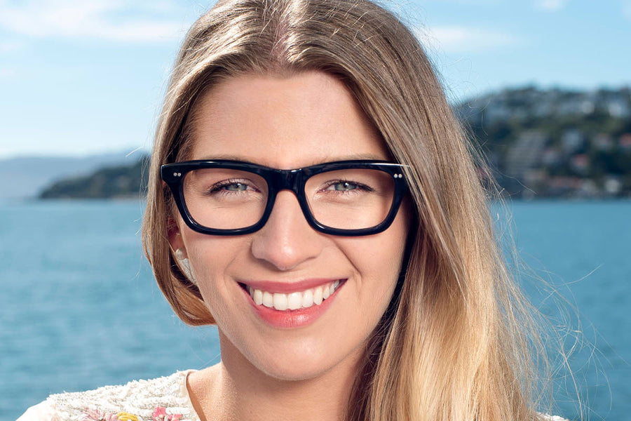 Smiling blond model wearing bold black geek chic acetate glasses frames by Mr Foureyes