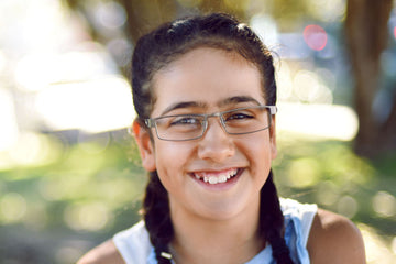 Smiling girl wearing metal children's glasses frames by Mr Foureyes (Marshall style)