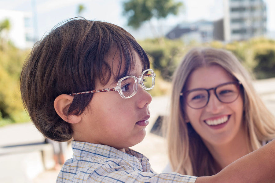 Child wearing clear acetate children's glasses frames by Mr Foureyes, standing at a blackboard, with a woman wearing glasses smiling at him