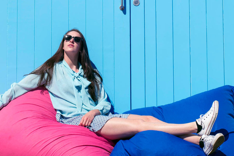 Woman lying back on bean bags against boat shed wearing sunglasses by Mr Foureyes
