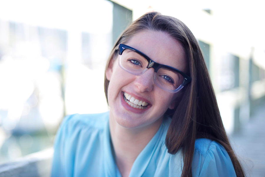 Smiling brunette model wearing bold black and clear geek chic acetate glasses frames by Mr Foureyes