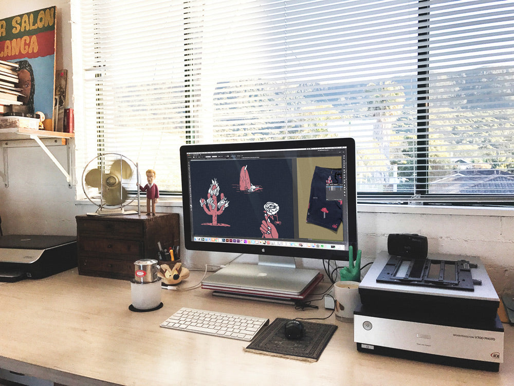 Artist Simon Perini's work space with boardshort design on computer