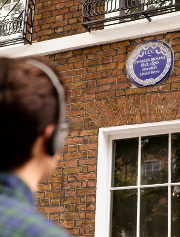 Tourist looking up at the Blue plaque commemorating Dickens.