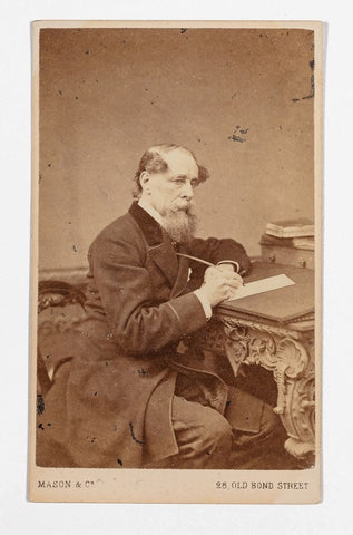 Carte de visite, front view with photograph of Charles Dickens seated at writing desk