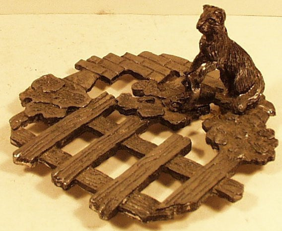 Metal trivet w/ cat spilling bucket dated 1986 Etzke