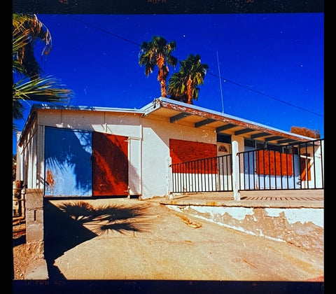 Mid-century architecture photography of an American Motel in California with blue sky and palm trees.