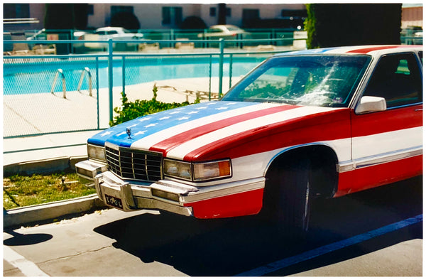 American flag painted car by the pool at a motel.