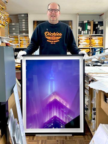 Richard Heeps in his home studio with a picture of New York.