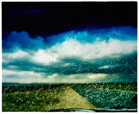 A blue tinted car window with rain on it looking out to a road landscape in South Africa.
