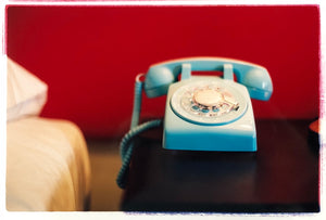 Interior photography of a blue vintage phone on a nightstand against a bold red wall taken in a mid-century Palm Springs hotel.