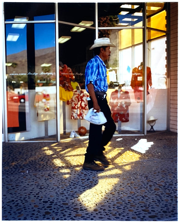 'Boutique' is street portrait, taken in Palm Springs, California. This piece is different from Richard Heeps' usual style, but everything fell into place: the light, the colours, and the man walking through the shot.