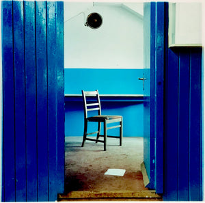 A blue painted room with a solitary chair visible through an open door