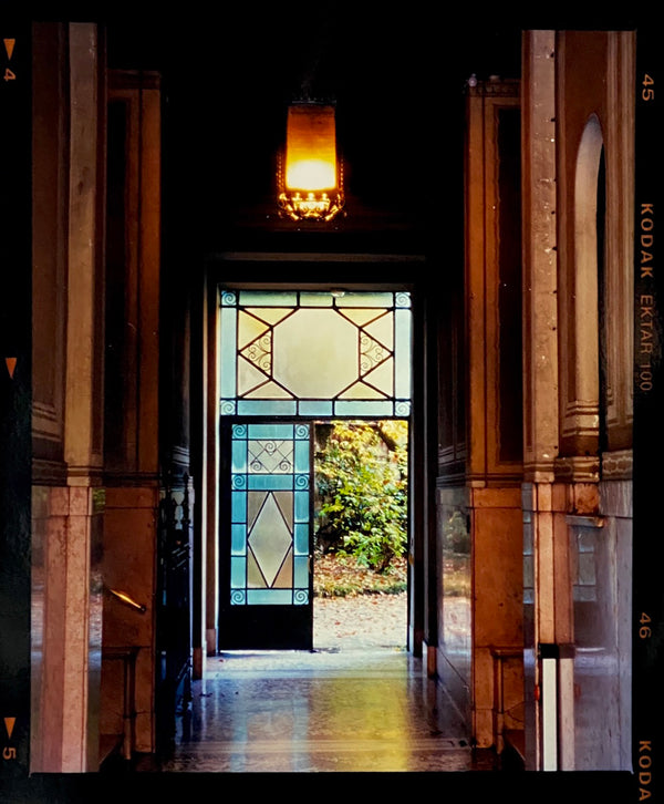 An Art Deco entrance hall in Milan, featuring blue stained glass panelling and marble flooring.
