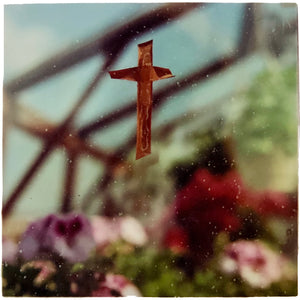 Abstract floral photograph with a crucifix in focus.