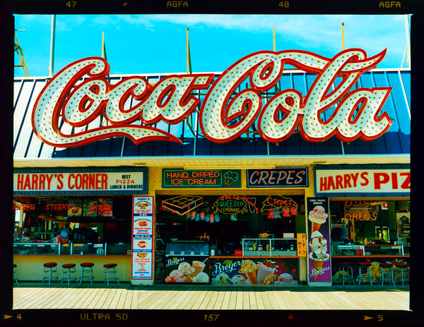 Harry's Corner, a photograph by Richard Heeps taken on the Wildwood boardwalk, featuring neon typography and the iconic Coca-Cola sign against a bright blue sky.