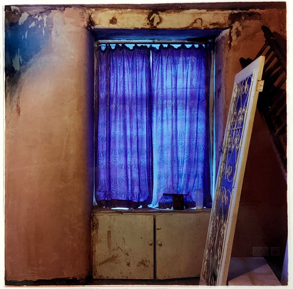 Interior photography of a dilapidated home with a purple curtain.