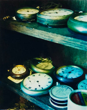 Vintage pocket watches on shelves.