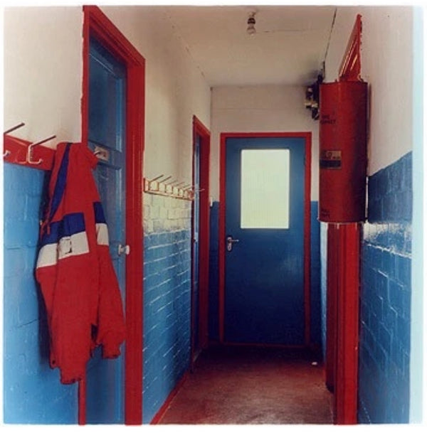 A jacket hangs from a row of coat pegs in a hallway painted blue, red and white.