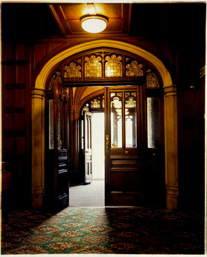 Bletchley Park entrance. Interior photography of a wooden panelled room with patterned carpet, stained glass and a warm light.