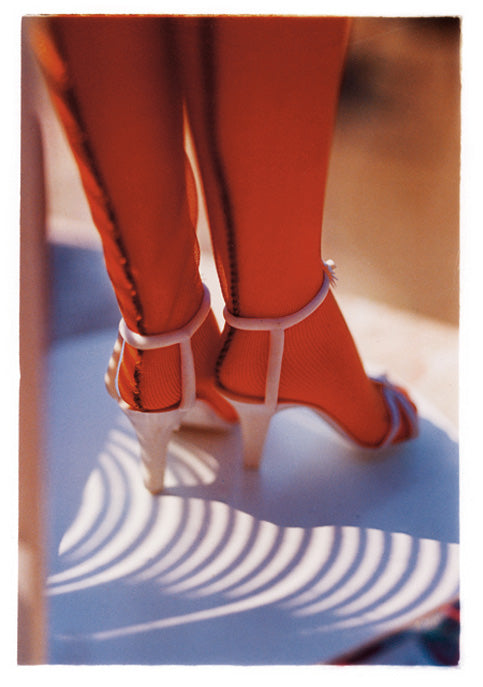 Photograph of a ladies calves, feet in strappy heels and seemed nude nylon tights. A shadow cast across the floor.
