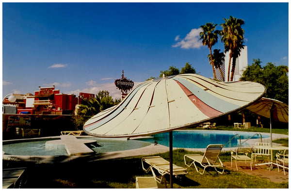 A vintage parasol, poolside at the El Morocco Motel, Las Vegas, Nevada, overlooked by palm trees, blue skies and iconic neon signs. Part of Richard Heeps' 'Dream in Colour' series.