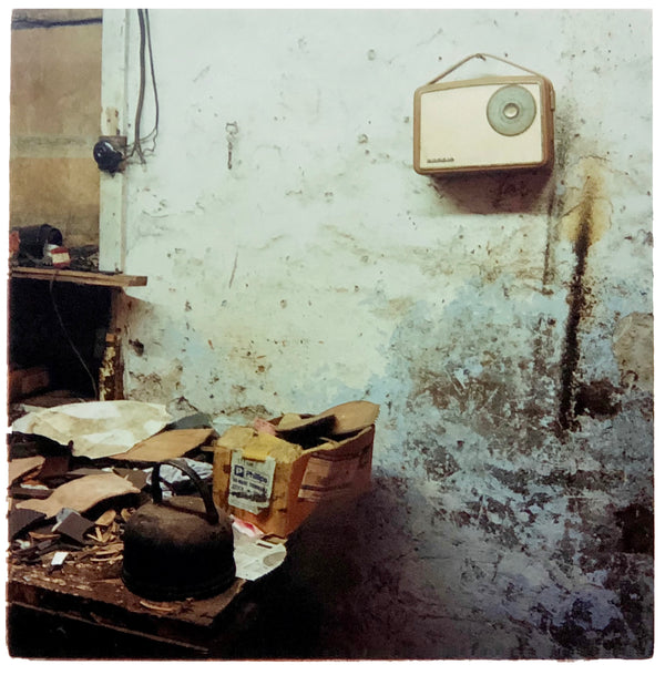 A vintage radio hangs on the wall in a dilapidated room.