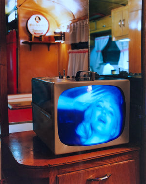 A vintage television with Marilyn Monroe's face on it set within a wooden panelled room.